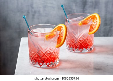 Two Cold Blood Orange Gin and Tonic Cocktails with Stirrers on Marble Bar Counter