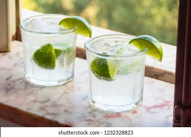 Two Cold Gin and Tonic or Vodka Tonic Cocktails Drinks with Limes in a Marble Windowsill