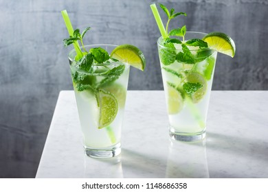 Two Cold Mojitos with Rum, Fresh Mint, and Lime Wedges in Glasses on Marble Bar Counter