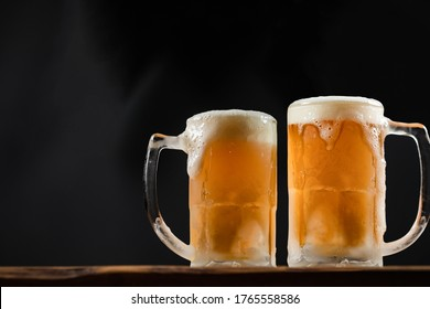 two cold mugs with beer, with overflowing foam, on wooden table and dark background, space for writing