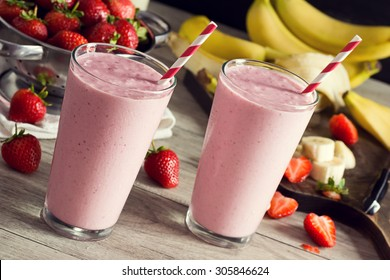 Two Cold Strawberry Banana Smoothies in Glasses with Ingredients on Kitchen Table