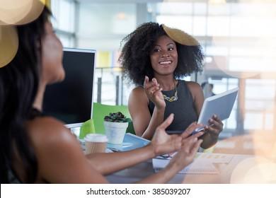 Zwei Kollegen diskutieren Ideen mit Tablet und Computer