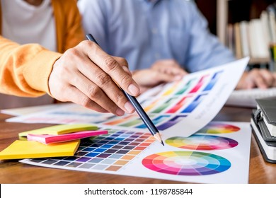Two colleague creative graphic designer working on color selection and color swatches, drawing on graphics tablet at workplace with work tools and accessories.