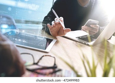 two colleague web designer discussing data and digital tablet and computer laptop with smart phone and design diagram on marble desk as concept