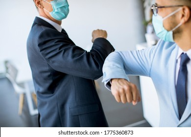 Two colleagues avoid a handshake when meeting in the office and greet with elbows bumping