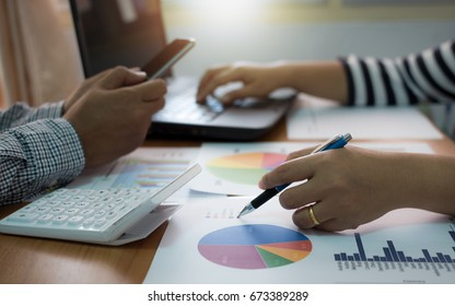 Two colleagues discussing data with mobile phone and laptop with marketing information graph on desk. Business team analyzing and strategy concept.