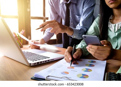 Two colleagues discussing data with smart phone and new modern computer laptop on desk table. Close up business team analysis and strategy concept.