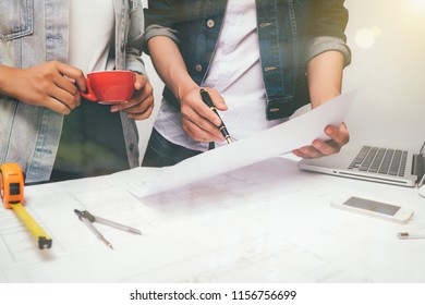 Two colleagues discussing data working and tablet working new start up project, laptop with on on architectural project at construction site at desk in office,warm colours sun light.