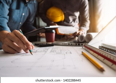Two colleagues discussing data working and tablet, laptop with architectural project at construction site at desk in office