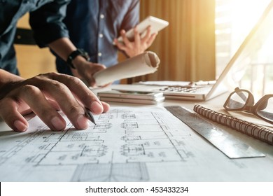 Two colleagues discussing data working and tablet, laptop with on on architectural project at construction site at desk in office