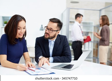 Two colleagues discussing document in working environment in office