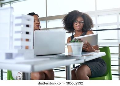 Zwei Kollegen diskutieren Ideen mit Tablet-Computern