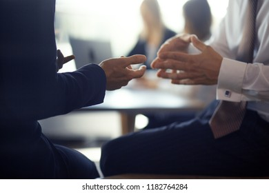 Two colleagues in formal clothes sitting on table in office. Having business conversation. Business concept.
