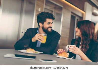 Two colleagues having breakfast in company's restaurant. Focus on the man