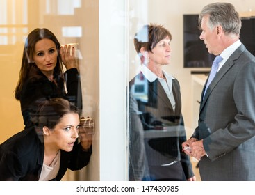 Two colleagues listening with a glass to the wall of the next office room where a man and a woman discuss their matters. Concept for eavesdropping, secrecy or curiosity