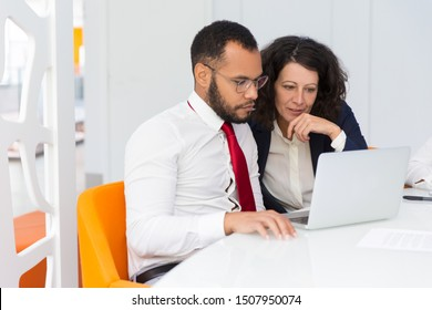 Two colleagues looking at laptop screen together. Business man and woman sitting and standing at conference table, using computer and talking. Consulting or mentorship concept