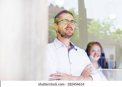 two colleagues looking through the window in office
