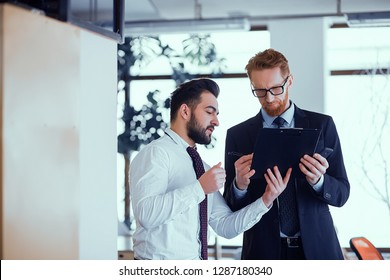 Two colleagues of male employees discuss a work plan on the eve of a business meeting. Koolega makes notes in the list of working current tasks
