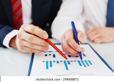 Two colleagues with pens pointing at document