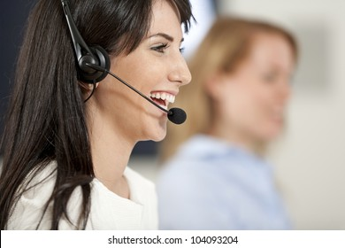 Two colleagues working in a busy call centre office.