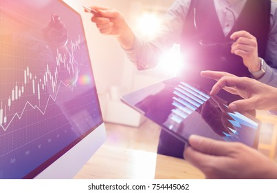 Two colleagues working on global financial trading strategy analysis using tablet and laptop.Modern business team innovation concept.Office project meeting with virtual forex graph and chart data.