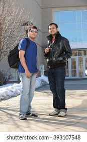 Two college students with backpacks standing outside building