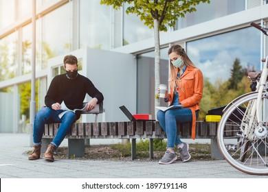 Zwei Studierende lernen, während sie soziale Distanz auf dem Campingplatz halten