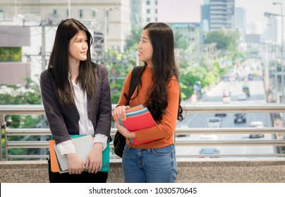 Two college students meeting and talking in city street