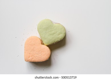 Two color alfajores cornstarch with heart shape on white background