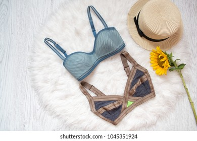 Two colored bra, straw hat and sunflower. White fur on the background