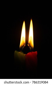 Two colored burning candles on a black background