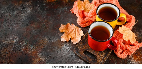 Two colored enamel tea cups, autumn maple leaves on rusty brown background