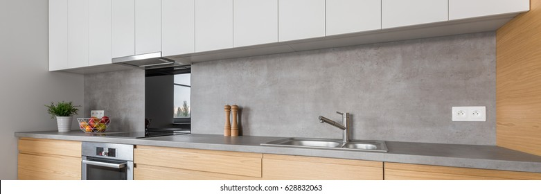 Two colored kitchen furniture with concrete worktop and steel appliances, panorama