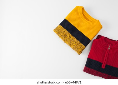 Two colored knitted sweaters on a white. Place for text.