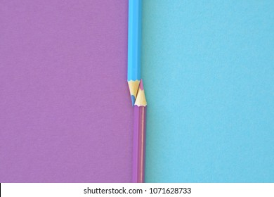 Two colored pencils split a picture in half in two different colors