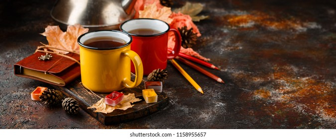 Two colored red and yellow enamel cups of tea, watercolors in cuvettes, colored pencils, autumn maple leaves and bumps on a rusty brown background