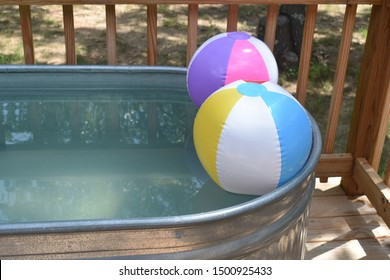 Two colorful beach balls float on the water in a stock tank swimming pool.