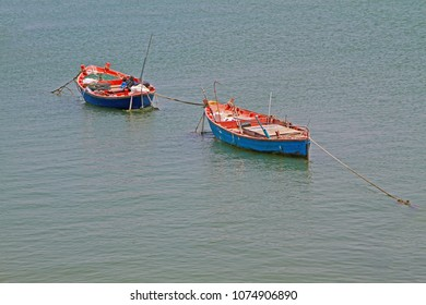 Two colorful blue and orange boat on water.