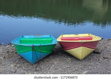 Two colorful boats await fishermen on the shore of a mountain lake