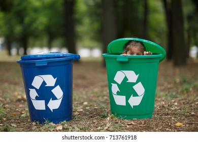 Two colorful boxes. Sitting boy have fun inside recyling waste bin outside. Concept of environmental protection.