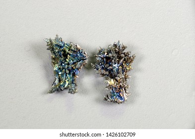 Two colorful crystalline pieces of the element Vanadium (V)