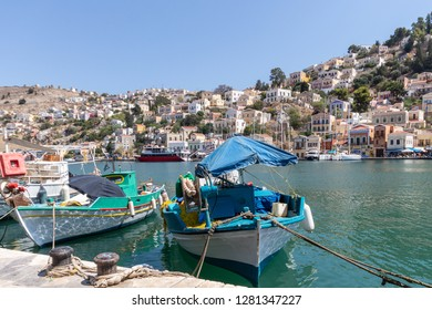 two colorful fishing boats with the skyline of the pictorial village of Symi in the background