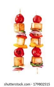Two colorful healthy grilled smoked tofu and vegetable kebabs on wooden skewers with cherry tomato, pepper and onion isolated on white