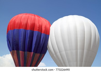 Two colorful hot air balloons against a blue sky.