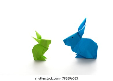 Two colorful origami Easter bunny rabbits made of paper in green and blue, of different sizes, perhaps parent and baby regarding each other, ready for Easter, isolated on white background