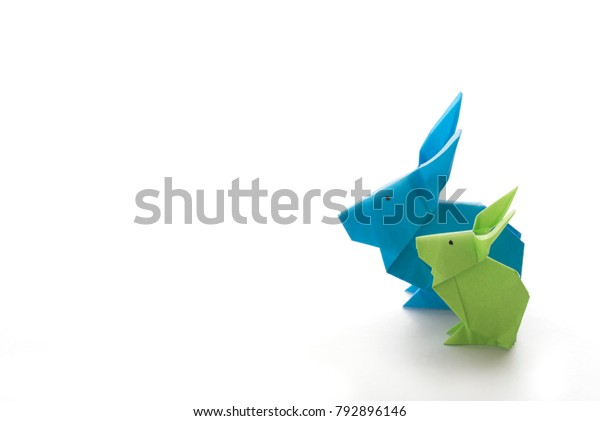 Two colorful origami Easter bunny rabbits made of paper in green and blue, of different sizes, perhaps parent and baby standing side by side, ready for Easter, isolated on white background