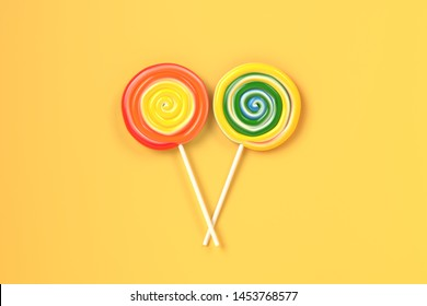 Two colorful spiral lolipop on yellow pastel background.sweet candy concept