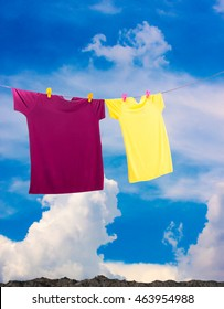 two a colorful summer t-shirt clothes  hanging on line for dry outdoor on sun and wind on blue sky background on surface soil a mountain.
