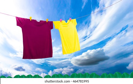two a colorful summer t-shirt clothes  hanging on line for dry outdoor on sun and wind on blue sky background.