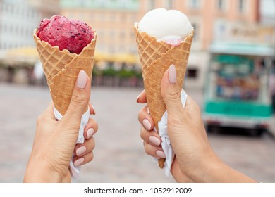 Two colorful tasty ice cream cones in hands